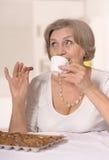 资深妇女吃巧克力糖 免版税库存照片
