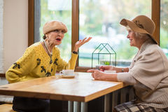 资深妇女和咖啡馆桌 免版税库存图片