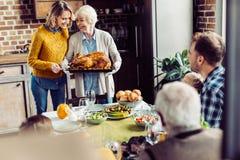 资深妇女和她的女儿运载的火鸡感恩晚餐的与他们 图库摄影