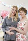 资深妇女和怀孕女儿微笑 库存图片