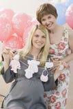 资深妇女和怀孕的女儿婴儿送礼会的 免版税库存照片