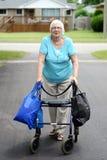 资深妇女和步行者超载与购物袋 库存照片