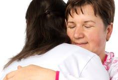 资深妇女和医生拥抱 免版税库存照片