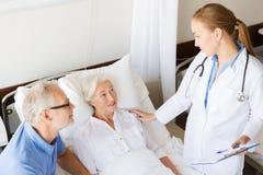 资深妇女和医生有剪贴板的在医院 免版税库存照片