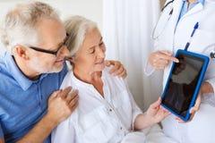 资深妇女和医生有片剂个人计算机的在医院 免版税库存照片