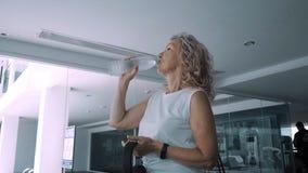 资深妇女喝从饮用水的水在健身房 免版税库存照片