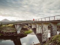 资深妇女在一座老桥梁站立在冰岛 免版税库存照片