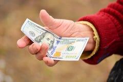 资深妇女在她的手上拿着金钱 金钱在老妇人手上 免版税图库摄影
