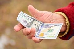 资深妇女在她的手上拿着金钱 金钱在老妇人手上 免版税库存照片