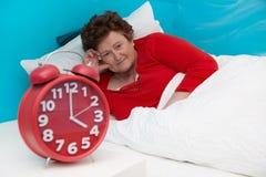 资深妇女在床上不适和遭受失眠或insomni 库存图片