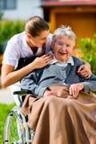 资深妇女在有护士的老人院在庭院里 免版税库存图片
