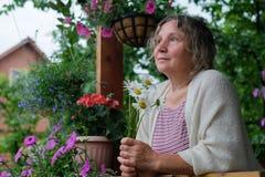 资深妇女在有花的绿色庭院里在手上 图库摄影