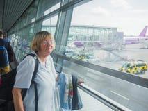 资深妇女在机场 免版税库存图片