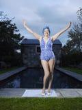 资深妇女在游泳衣支持的游泳池边 免版税库存照片