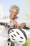 资深妇女在登山车把手倾斜  免版税图库摄影