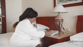 资深妇女坐一张床在一件白色浴巾的一家旅馆和拾起电话和拨号盘 t 股票视频
