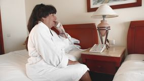 资深妇女坐一张床在一件白色浴巾的一家旅馆和采取电话 t 股票录像