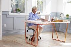 资深妇女坐在书桌并且研究在内政部的膝上型计算机 免版税库存图片