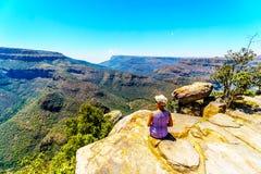 资深妇女坐峭壁` s边缘,享受布莱德河峡谷的看法从观点在三Rondavels 图库摄影