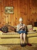 资深妇女坐沙发编织 库存照片