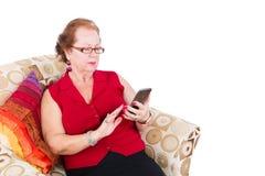 资深妇女坐长沙发使用她的电话 免版税库存图片