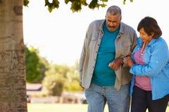 资深妇女帮助的丈夫,他们在公园一起走 免版税库存照片