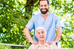 给资深妇女按摩的老年医学的护士 免版税库存图片