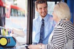 资深妇女搭乘公共汽车和购买票 图库摄影