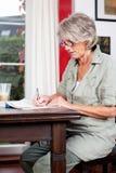 资深妇女文字笔记在家 免版税库存照片