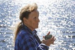 资深妇女有一份热的饮料由湖边 免版税库存图片