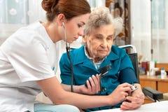 资深妇女测量的血压  免版税库存照片