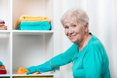 资深妇女清洁房子 免版税库存照片