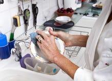 资深妇女清洁板材的播种的图象在厨房里 免版税库存图片