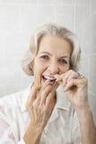 资深妇女清洁牙齿的牙画象在卫生间里 库存照片