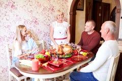 资深妇女用一个庆祝的家庭的烤火鸡在轻的背景 传统概念 复制空间 库存图片
