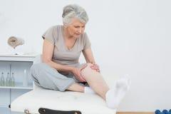 资深妇女用她的在一个痛苦的膝盖的手 免版税库存照片