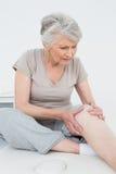 资深妇女用她的在一个痛苦的膝盖的手 免版税图库摄影