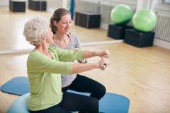 资深妇女由在健身房的个人教练员协助了 免版税图库摄影