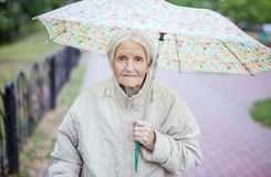 资深妇女画象在伞下 库存照片
