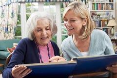 资深妇女看与成熟女性邻居的象册 免版税库存照片