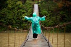 资深妇女穿过河的60岁由取决于的桥梁在森林里 库存图片