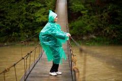 资深妇女穿过河的60岁由取决于的桥梁在森林里 免版税库存图片