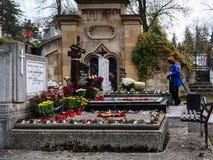 资深妇女站立在致以对已故的亲戚的坟墓尊敬 免版税库存图片