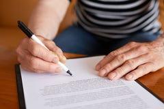 资深妇女署名文件的手 图库摄影
