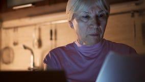 资深妇女自由职业者用途膝上型计算机在从家庭办公室的晚上 努力劳累过度的女实业家工作 股票视频