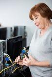资深妇女观察计算机缆绳 图库摄影