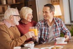 资深妇女观看她的儿子的和丈夫食用早餐 免版税库存图片