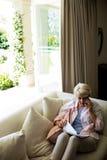 资深妇女谈话在手机,当检查一个文件在客厅时 库存照片