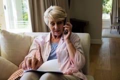 资深妇女谈话在手机,当检查一个文件在客厅时 库存图片