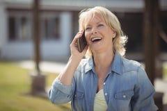 资深妇女谈话在手机他的房子外 库存图片